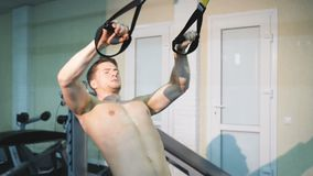 A man shaking hands in the hall TRX, a man doing exercises on his hands