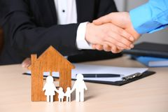 Man shaking hands with real estate agent at table, focus on family and house figures. Home insurance royalty free stock images