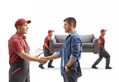 Man shaking hands with a removal guy, movers carrying a couch royalty free stock image
