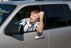 Man in his vehicle with Road Rage. Man shaking his fist in a fit of Road Rage stock photo