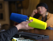 Man shaking a martini cocktail. Close up view of a barman shaking a martini cocktail in a colourful blue and yellow cocktail shaker watched by a patron at the royalty free stock photo