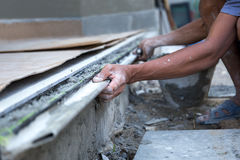 Man shape the edge of the floor with plasterer concrete cement Royalty Free Stock Photos