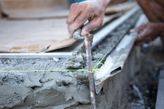 Man shape the edge of the floor with plasterer concrete cement Stock Photo