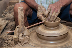 A man shapes pottery as it turns on a wheel. Pottery is a delicate and requires skilled in the art they made Stock Image