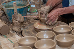 A man shapes pottery as it turns on a wheel. Pottery is a delicate and requires skilled in the art they made royalty free stock photography