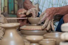 A man shapes pottery as it turns on a wheel. Pottery is a delicate and requires skilled in the art they made Royalty Free Stock Images