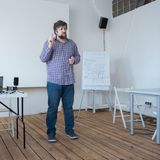 Filmmaking school concept. Professor lecturing at classroom with wooden floor. Caucasian teacher standing in lecturing royalty free stock photo