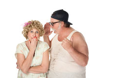 Man sharing a secret with a woman. Funny man sharing a secret with a woman on white background Stock Photography