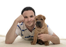 Man with sharpei puppy isolated. Young caucasian man with sharpei puppy laying on a white blanket with white isolated background Royalty Free Stock Photos