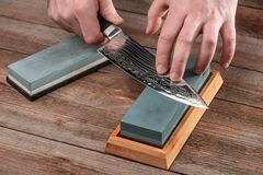 Free Man Sharpening A Japanese Chef`s Knife With A Wet Whetstone Royalty Free Stock Images - 186241659