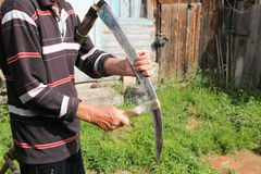 Man sharpening a scythe before mowing royalty free stock photo
