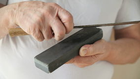 Man sharpens knife front view stock video footage