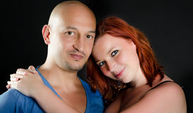 Man with shaved head a girl with red hair. Portrait of a good looking men and a pretty redheaded woman Royalty Free Stock Images