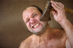 Man shaves with an ax Royalty Free Stock Image