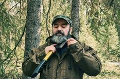Man Shaves beard ax. Brutal bearded man Shaves beard ax stock image