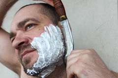 Man shaves his beard with a knife. On a gray background stock photography