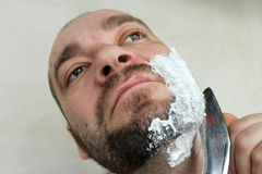 Man shaves his beard with a knife. On a gray background royalty free stock image