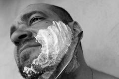 Man shaves his beard with a knife. On a gray background. Black and white photo stock image