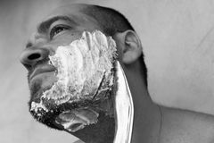 Man shaves his beard with a knife. On a gray background. Black and white photo royalty free stock photography