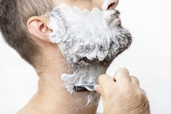 Man shaves his beard with a razor. Man is shaving his beard with a razor. Young man has face full of shaving soap foam royalty free stock photography