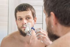 Man shaves his beard very strong. A man shaves his beard very strong stock photos