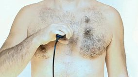Man shaves his chest. With an electric shaver on white background stock video footage