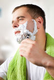 Man shaves his face Stock Images