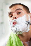 Man shaves his face Stock Photo
