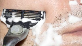 A man shaves the machine. Background shave with shaving cream royalty free stock photography