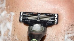 A man shaves the machine. Background shave with shaving cream stock photo