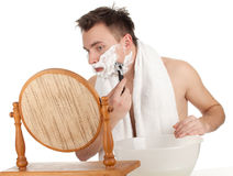 Man shaves in the mirror Stock Photo