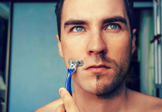 Man shaves in the morning with a straight razor stock photography