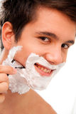 Man shaves with a razor blade and shaving cream Stock Photos
