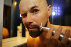 Man shaves trimmer. Portrait of a man shaves trimmer royalty free stock image
