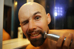 Man shaves trimmer. Portrait of a man shaves trimmer royalty free stock photos