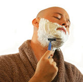 Man Shaving. Young man wet shaving with razor in dressing gown Stock Image