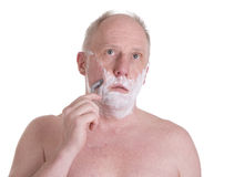 Man Shaving. A man shaving looking into the mirror royalty free stock photo