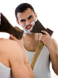 Man shaving with ax,reflection in mirror Royalty Free Stock Image