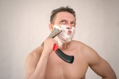 Man is shaving by axe. Frown man with brutal face is shaving with axe shaver in the bathroom stock images
