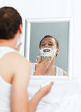 Man shaving in bathroom. Happy young man shaving in bathroom Royalty Free Stock Image