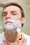 Man shaving in the bathroom. Handsome man shaving in the bathroom Stock Photos