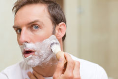 Man shaving in the bathroom. Handsome man shaving in the bathroom Stock Photography