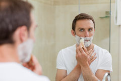 Man shaving in the bathroom. Handsome man shaving in the bathroom Royalty Free Stock Photo