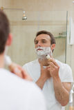 Man shaving in the bathroom Stock Photos