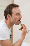 Man shaving in the bathroom. Handsome man shaving in the bathroom Royalty Free Stock Images