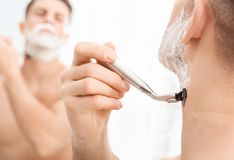 Man shaving in bathroom,. Closeup Royalty Free Stock Images