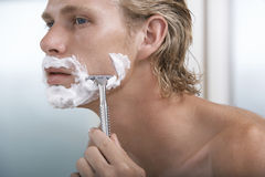 Man Shaving In Bathroom. Closeup of handsome young man shaving in bathroom Royalty Free Stock Photo