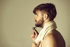 Man shaving in bathroom with safety razor and bathing towel. Copy space royalty free stock photo
