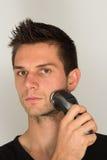 Man shaving beard in face. With an electric razor Stock Photos