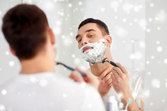 Man shaving beard with razor blade at bathroom Stock Image